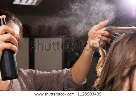 hairdresser fixing a coiffure with ringlets of a young girl using a hair spray in a beauty salon. concept of professional stylist training