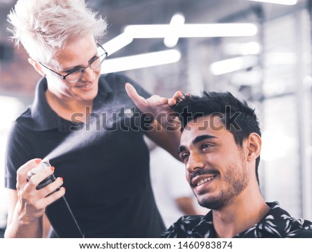 Hairdresser fixing a coiffure with ringlets of a young man using a hair spray in a beauty salon. Concept of professional stylist training