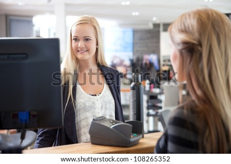 Hairdresser helping client at beauty salon.