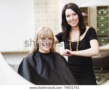 Hairdresser in action with blond customer - stock photo