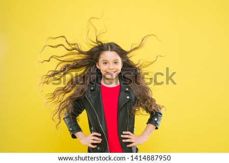 Hairdresser is a girls best friend. Cute little girl with long wavy hair happy smiling on yellow background. Kids hairdresser. Hairdresser salon for children. My hairdresser is good with her hands.