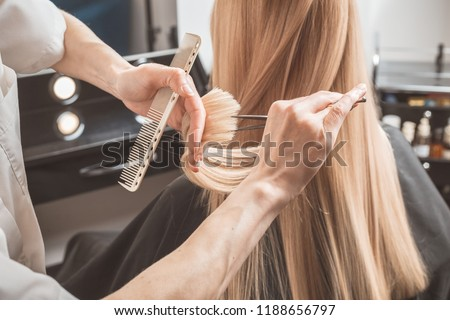 Hairdresser is cutting long blond hair in hair salon