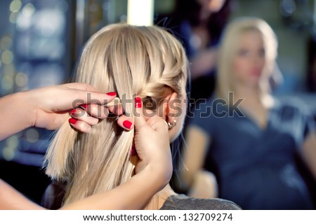Hairdresser make French braids   in beauty salon.