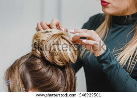 Hairdresser makes upper bun hairstyle close-up on brown hair of beautiful woman