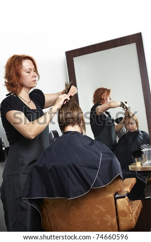 hairdresser making haircut at beauty salon
