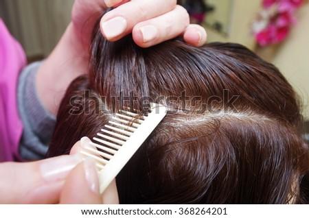 hairdresser prepares customer for haircut in a salon #368264201
