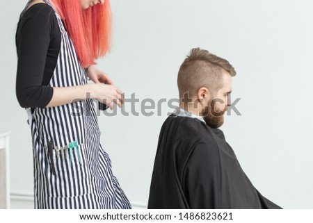 Hairdresser, stylist and barber shop concept - woman hairstylist cutting a man