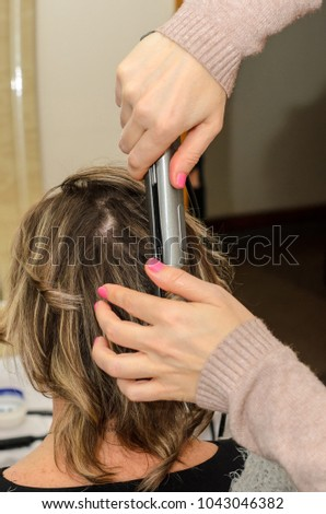 hairdresser using hair curlers curls the short blond hair of a woman #1043046382