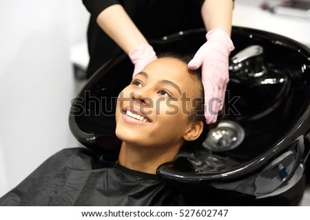 Hairdresser washing and massaging her head. Hairdresser washing hair woman  #527602747