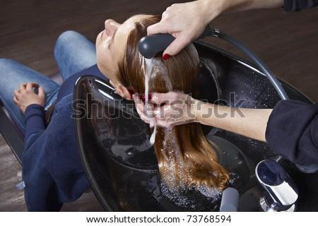 Hairdresser washing woman hair