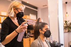Hairdresser with face mask combing the client's hair with hairspray. Reopening with security measures of Hairdressers in the Covid-19 pandemic