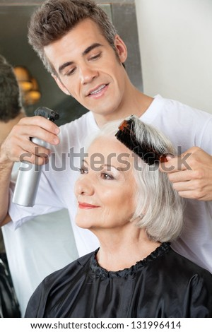 Hairdresser with spray and brush setting up female client's hair