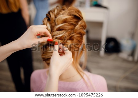 Hairdresser woman conducts training for pupil in salon, weaving braid hair, wedding styling.