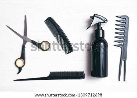 Hairdresser work table flatlay background. A various hairdressing tools such a hairbrushes, sprayer and a scissors on a white wooden board.