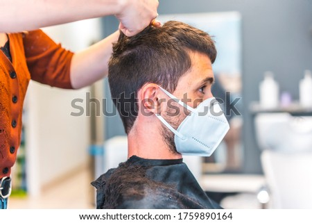 Hairdressers after the Coronavirus pandemic. Hairdresser with face mask and protective screen, covid-19. Social distance, new normality. Young caucasian man at the hairdresser receiving a haircut.