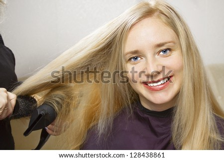 Hairdressers Hands Drying Long Blond Hair With Blow Dryer