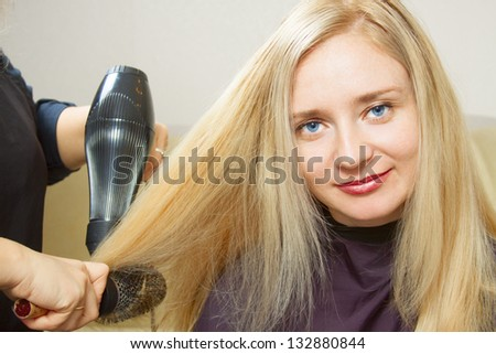 Hairdressers hands drying long blond hair with blow dryer and round brush