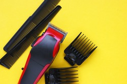 Hairdressers tool. Hair clipper close-up on a yellow background with nozzles of different sizes.