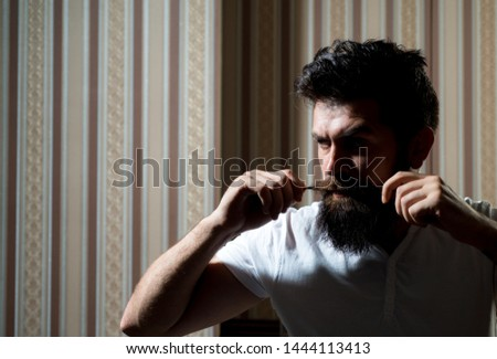 Hairdressers work for a handsome guy at the barber shop. Barber shop design. Portrait bearded man. Balm on dry body parts to moisturize skin. Professional hairstylist in barbershop interior