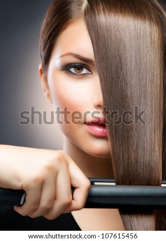 Hairdressing. Hair Straightening Irons.Beautiful Woman with Long Straight Hair. Healthy Hair. Hairstyling.