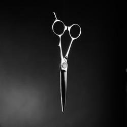 Hairdressing scissors on a black background. Black and white photography.