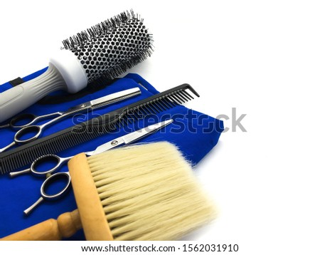 Hairdressing scissors, thinning scissors, comb, brush and hairdresser cape isolated on white background. Composition of hairdressing tools for a beauty salon. Set for cutting hair.