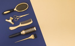 Hairdressing tools on a blue background and a yellow sheet with space for text. Gold hair salon accessories, comb, scissors, hair clip.