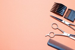 Hairdressing tools, scissors and comb on an orange background, a replica of the space