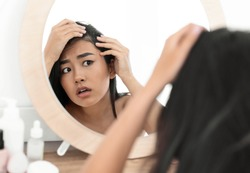 Hairloss concept. Young troubled asian woman checking for thinning hair in mirror at home