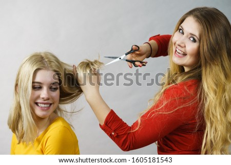 Hairstyle and haircut. Young female barber holding scissors tool ready to trimming hair her friends. Two girls creating new hairdo coiffure