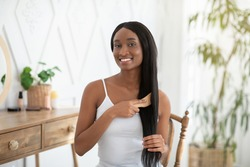 Hairstyle, daily hair care at home during covid-19 lockdown. Cheerful millennial african american lady combing long beautiful straight hair in bedroom interior in morning, copy space, indoor