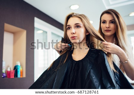 Hairstylist deciding with the young female customer what haircut to do in hairdressing parlor. Two pretty blondes discussing a new hairstyle.