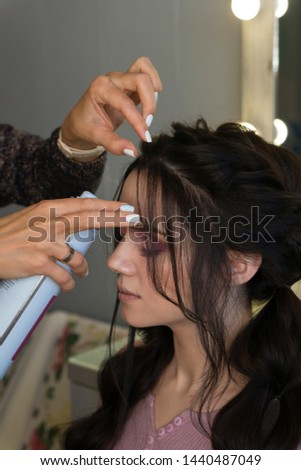 Hairstylist fixes textured tress using hair spray. Hairdressing services. Process of creating hairdo. Hairdresser makes hairstyle to client. Beauty industry