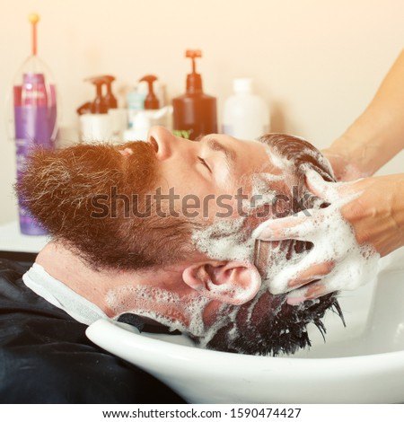 Hairstylist hairdresser washing customer hair - brutal man relaxing in hairdressing beauty salon. Hairdressers wash head to the client. Man at barbershop.