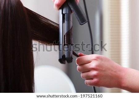 Hairstylist hands with electric roller curler. Hairdresser curling hair of female client. Woman in hairdressing beauty salon.