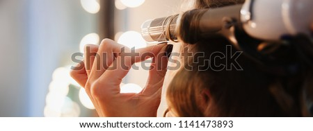 Hairstylist make beautiful curls with curler on light-brown client's hair. Closeup beauty salon background: master's hand holding equipment and customer's hair.