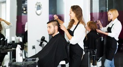 Hairstylist makes the haircut for young man in the hairdressing salon
