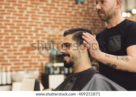 Hairstylist making men\'s haircut to an attractive man in the beauty salon.