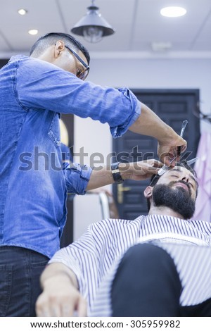 hairstylist on a beard shaving session and a customer on a barber chair on the barber shop - focus on the barber face