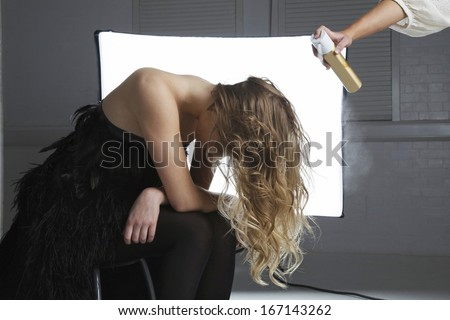 Hairstylist spraying hair product on model\'s hair