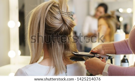Hairtician twirls curls with flat iron hair. Back view. Hairdressing services. Creation of evening hairstyles fashionable stylish women's hairstyles. Hair styling process. Courses in hairdressing.