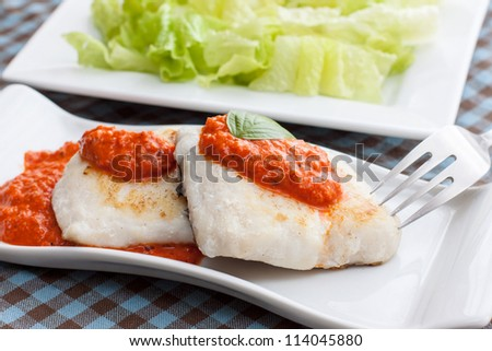 hake fillet with pepper sauce on white tray - stock photo