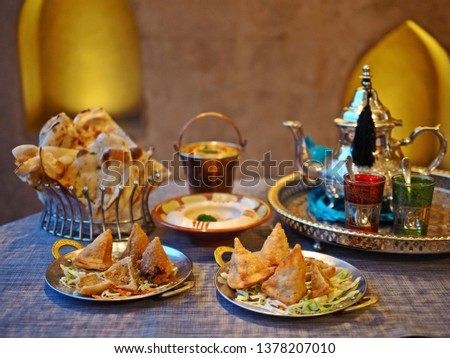 Halal chicken samosas served with vegetable on the dining table with blurred dal makhani, hummus, naan bread, tea pot. Ramadan dish cooked with blessing meat, food preparation for the iftar meal. #1378207010
