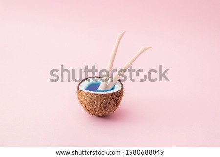 Half a coconut with blue water and plastic doll legs protruding from the coconut.