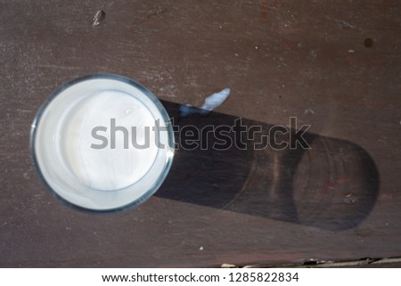 Half a glass of fresh milk on wooden texture, background, Light & shadow, Close up shot, Selective focus, Breakfast table #1285822834