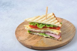 Half a sandwich on a wooden plate. Sandwich filling consists of ham, cheese, lettuce and sliced tomato. Close-up. Light background. Free space for text.