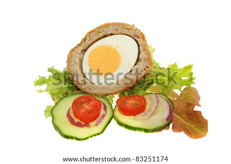 Half a Scotch egg and salad garnish isolated against white