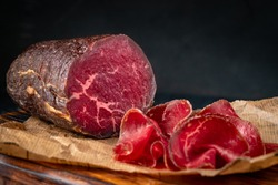 Half a smoked bresaola and cut pieces on a chopping Board. Italian Antipasti, rustic style