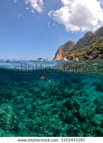 Half and half picture of a man diving in Cala Embasset (Mallorca) with crystal clear turquoise waters and a sunny day with some boats on the surface, taken with an action camera and a dome port