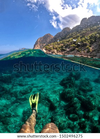Half and half picture of a man swimming with his diving fins in Cala Embasset (Mallorca) with crystal clear turquoise waters and a sunny day, taken with an action camera and a dome port